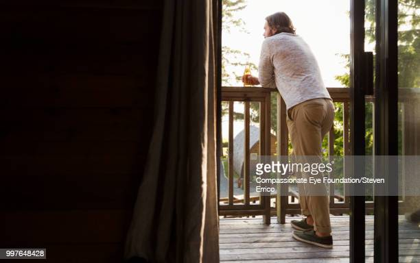 Man leaning on balcony looking at view