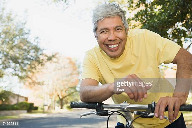 Man leaning on bicycle handlebars