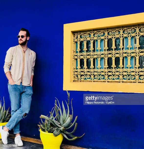 man leaning on blue wall - homme marocain photos et images de collection