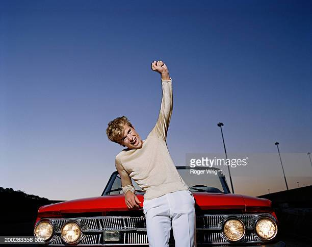 Man leaning on bonnet of convertible car, arm raised, cheering