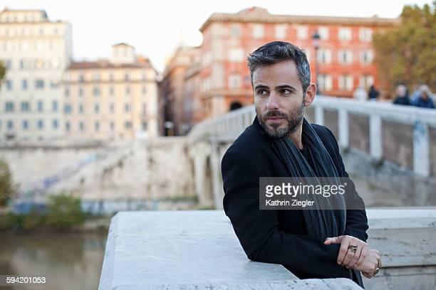 man leaning on bridge, Rome, Italy