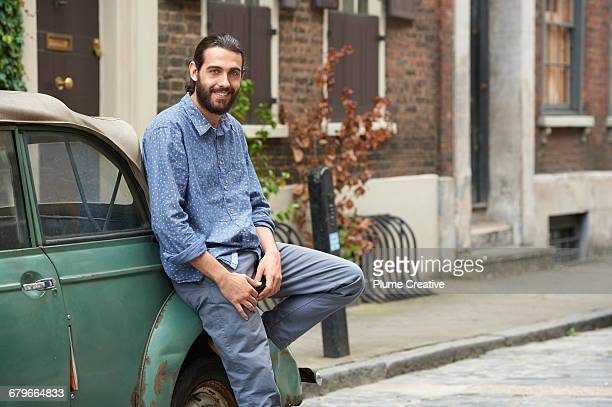 man leaning on car - rusty old car stock pictures, royalty-free photos & images