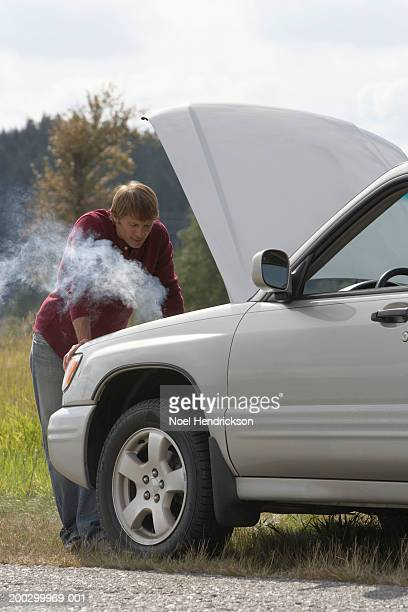 Man leaning on car with bonnet open at roadside