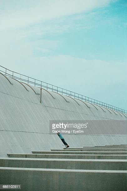 Man Leaning On Concrete Wall Against Sky