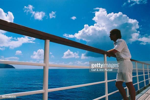man leaning on cruise ship railing - geländer stock-fotos und bilder