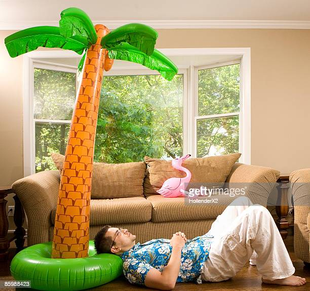 man leaning on fake palm tree in house