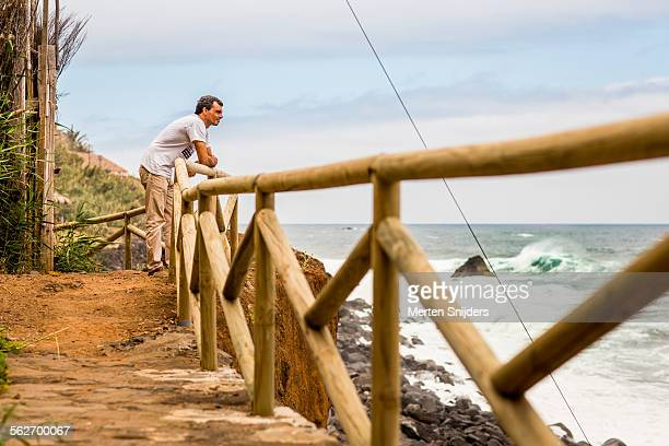 man leaning on fence observing waves in ocean - merten snijders stock-fotos und bilder