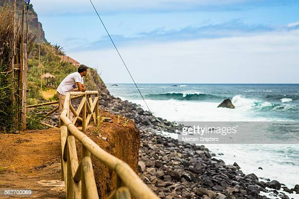 man leaning on fence observing waves in ocean - merten snijders stockfoto's en -beelden