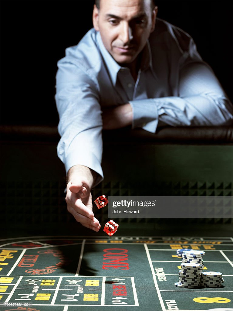 Man leaning on gaming table throwing dice : Stock Photo