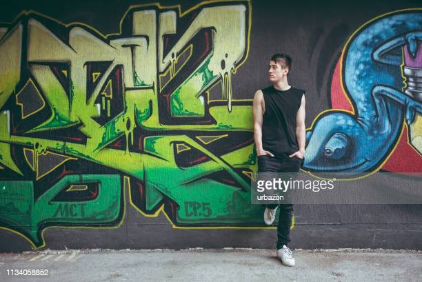 man leaning on graffiti wall - graffiti foto e immagini stock
