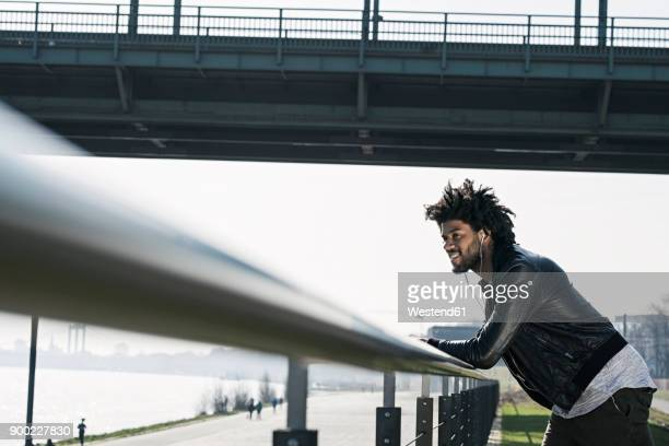 Man leaning on handrail watching over river