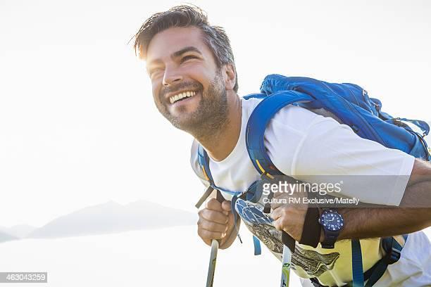 Man leaning on hiking poles smiling, Tyrol, Austria