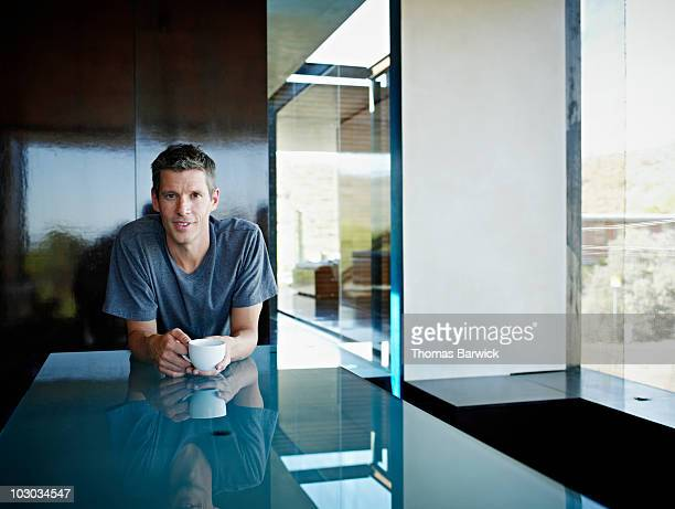 man leaning on kitchen counter with coffee cup - image photos et images de collection