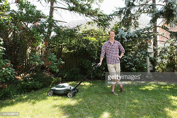 man leaning on lawnmower - lawn mower stock pictures, royalty-free photos & images