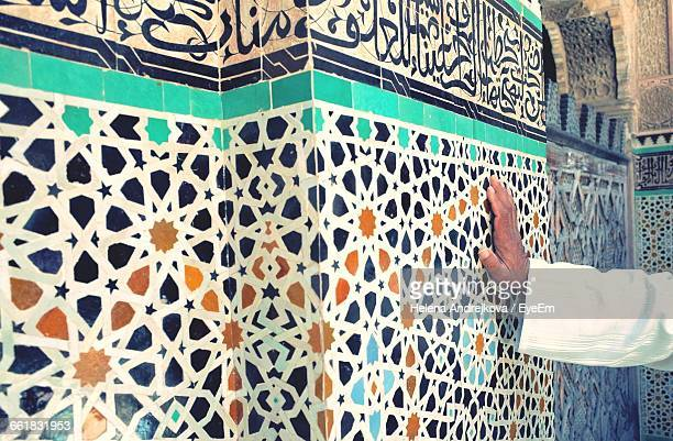 Man Leaning On Mosaic Tiled Wall