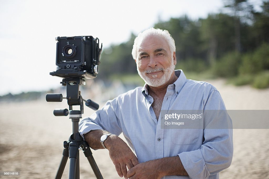 Man leaning on old-fashioned camera at beach : Foto de stock