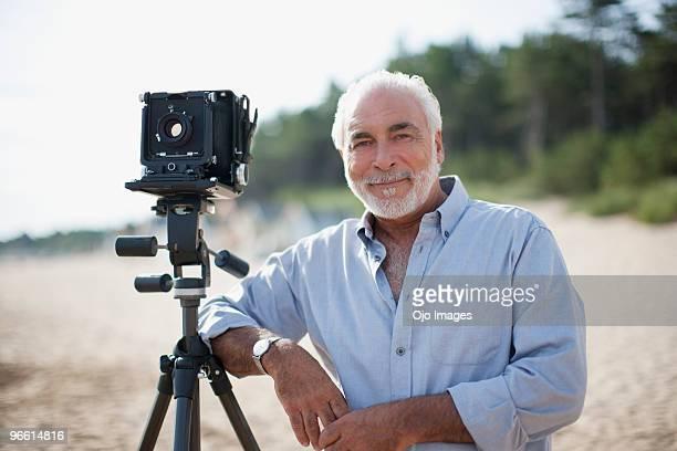 man leaning on old-fashioned camera at beach - gesticulando - fotografias e filmes do acervo