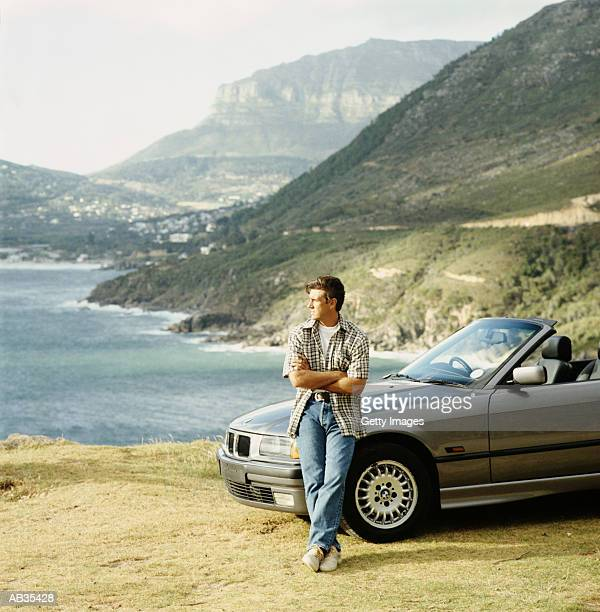 Man leaning on parked convertible car, looking out at view