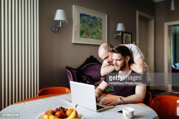 Man Leaning On Partner While Looking At Photos Together