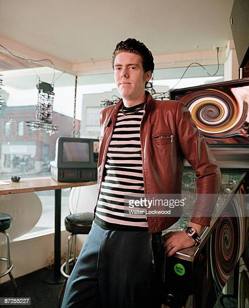 Man leaning on pinball machine