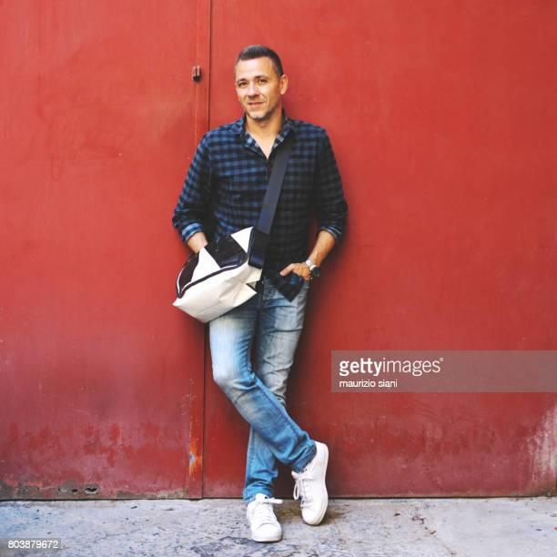 man leaning on red metal garage door - crossbody bag photos et images de collection