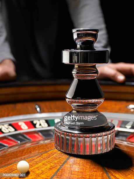 Man leaning on roulette table, (focus on wheel)
