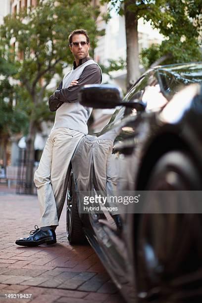 Hombre apoyarse en coche deportivo