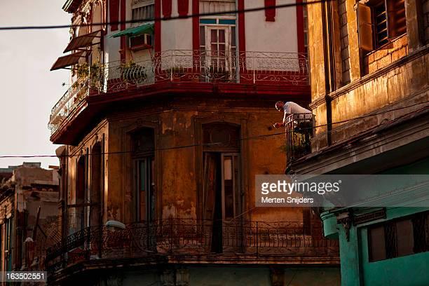 man leaning on streetside balcony rail - merten snijders stockfoto's en -beelden