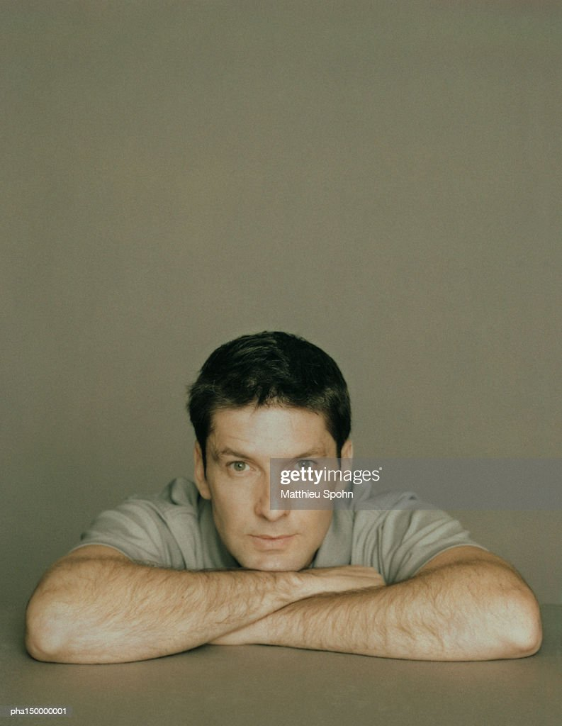 Man leaning on table, resting chin on crossed arms, portrait : Stockfoto