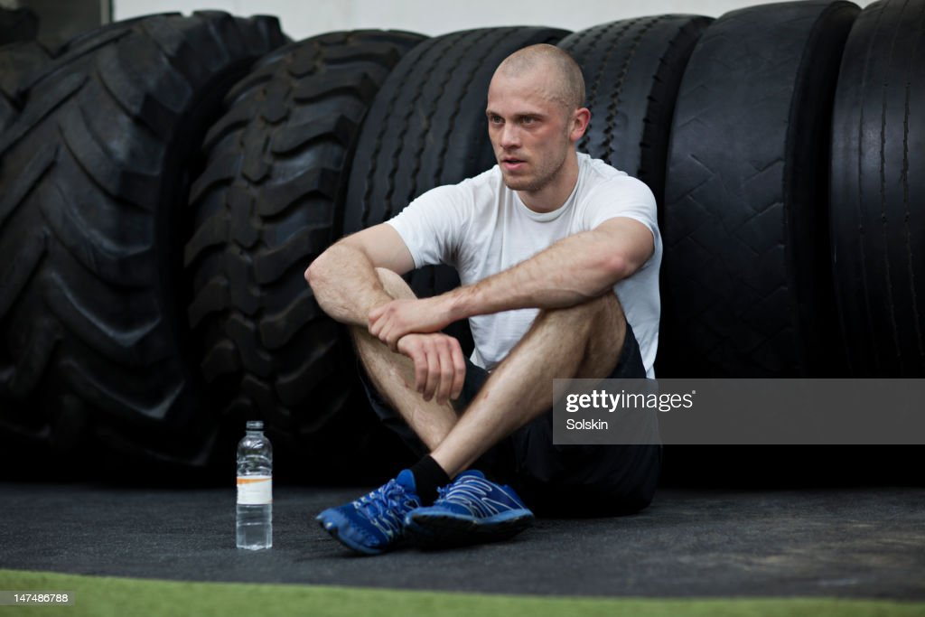 Man leaning on tires in gym center : Stock Photo