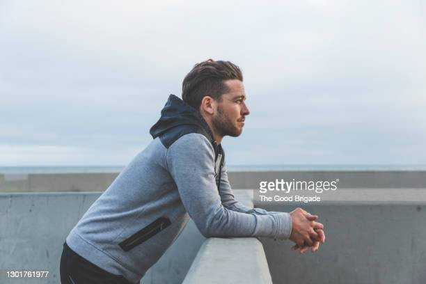 man leaning on wall looking out to sea - tranquil scene stock pictures, royalty-free photos & images