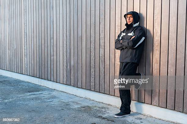 Man leaning on wooden wall