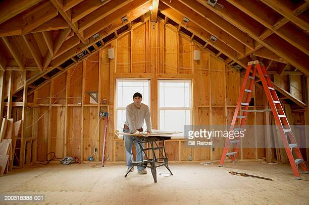 Man leaning on workbench in house under construction, portrait