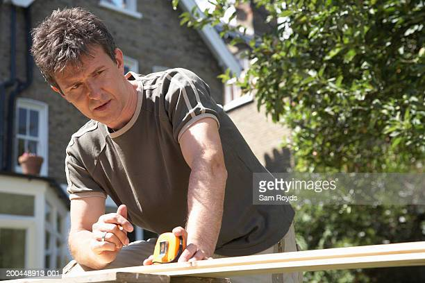 Man leaning on workbench set up in garden, holding tape measure