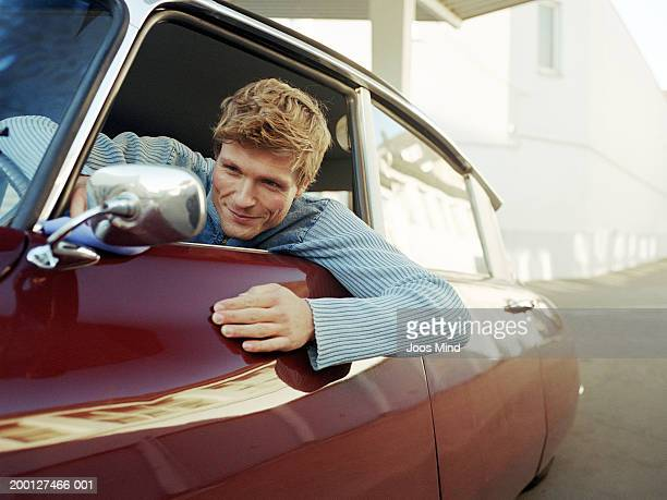 Man leaning out car window looking in wing mirror, close-up