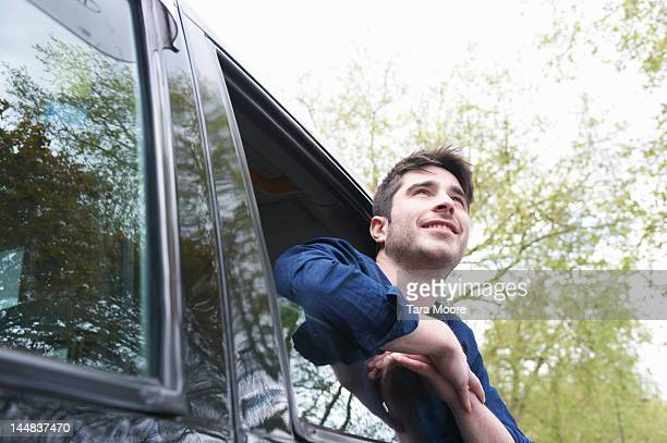 man leaning out of car and smiling - newtechnology stock pictures, royalty-free photos & images