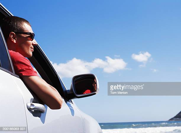 Man leaning out of car window facing ocean, low angle view
