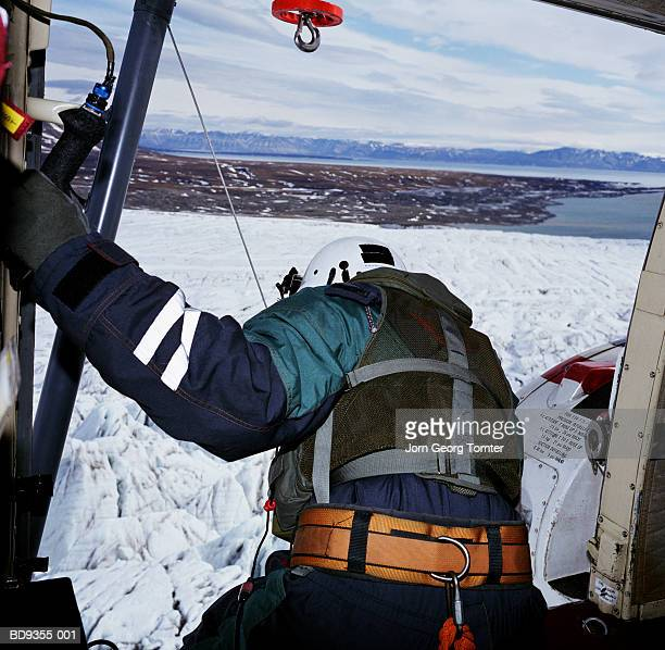 Man leaning out of helicopter, rear view