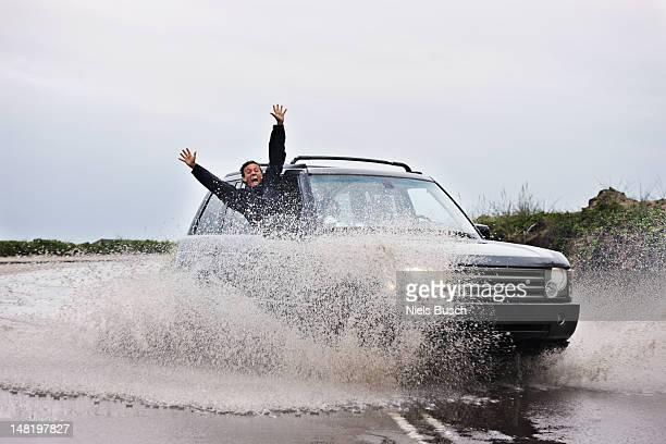 Man leaning out of splashing car
