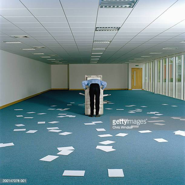 Man leaning over photocopier in large room, papers on floor, rear view