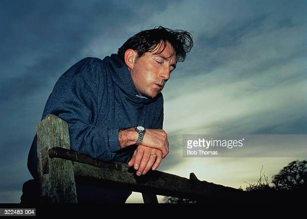 Man leaning,exhausted,on gate, sweating heavily,eyes closed