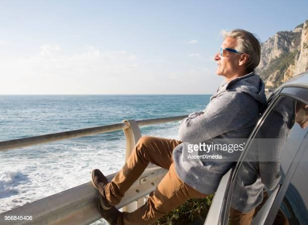 l'uomo si appoggia all'auto e si affaccia sul mar mediterraneo - 55 59 anni foto e immagini stock