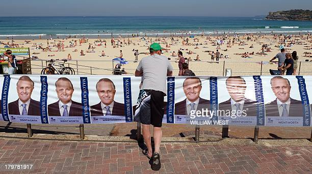 A man leans against political posters outside a polling booth at Sydney's Bondi Beach on September 7 in Australia's general election Polls show...