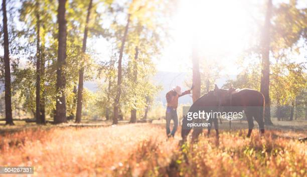 man leans against tree while he and his horse rest - montana western usa stock pictures, royalty-free photos & images