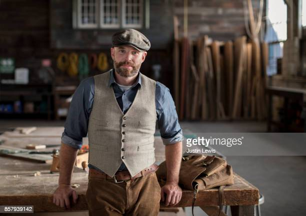 Man Leans Against Workbench, Having Just Arrived to the Carpentry Studio for a Day's Work