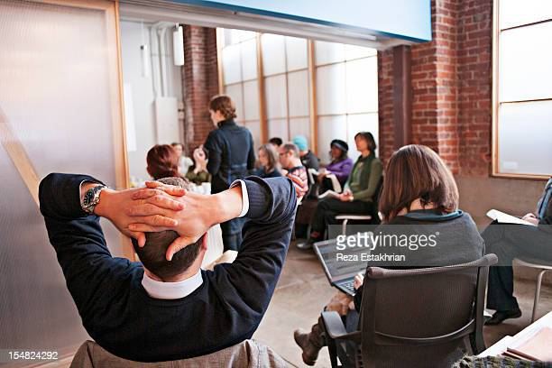 Man leans back during business meeting