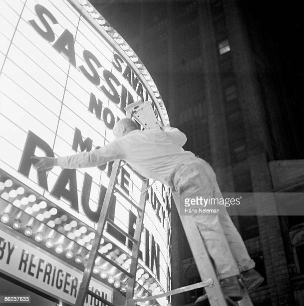 Man leans forward as he stands atop a ladder to attach letters to a movie theatre marquee, New York, New York, mid 1969. The movies titles that he is...