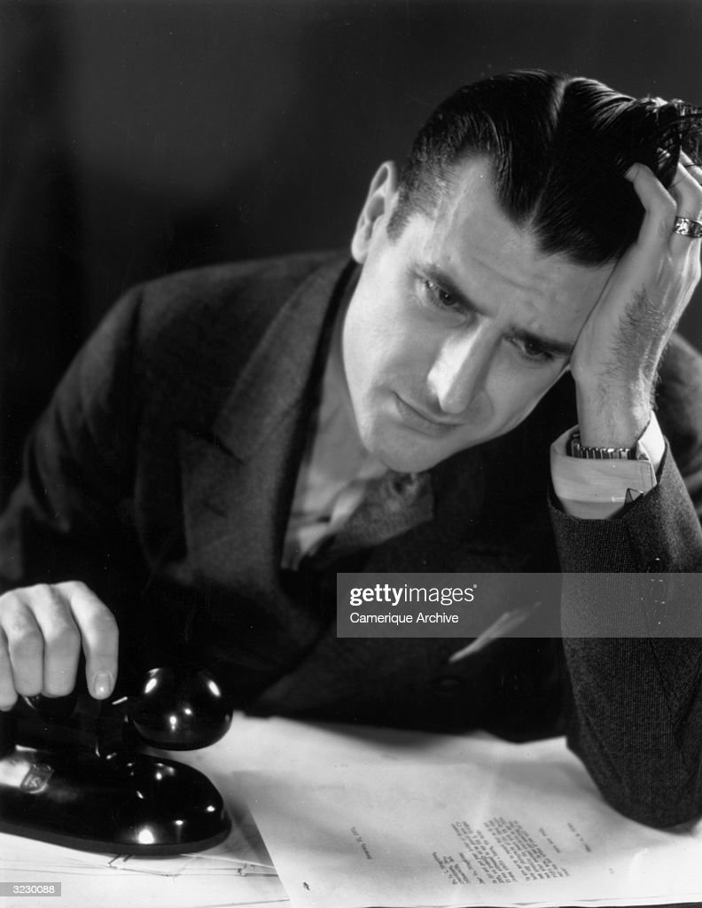 A man leans his head on his hand and knits his brow with concern while holding a telephone receiver. He props his elbow on top of a business letter.