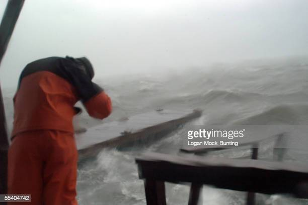 A man leans into the wind while looking over docks that were broken apart by the heavy winds and rough waters brought on by Hurricane Ophelia as it...