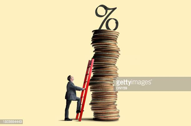 man leans ladder against tall stack of coins topped with interest rate symbol - percentage sign stock pictures, royalty-free photos & images